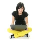Muchacha que trabaja en su computadora portátil. Imagenes de archivo
