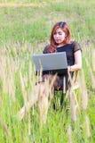 Muchacha que trabaja en su ordenador portátil afuera Imagen de archivo libre de regalías