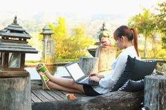 Muchacha que trabaja en su ordenador portátil afuera Fotos de archivo libres de regalías