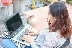 Muchacha que trabaja en su ordenador portátil afuera Fotos de archivo