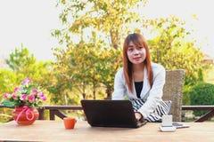 Muchacha que trabaja en su ordenador portátil afuera Imágenes de archivo libres de regalías