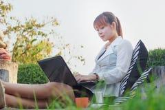 Muchacha que trabaja en su ordenador portátil afuera Fotografía de archivo