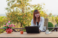 Muchacha que trabaja en su ordenador portátil afuera Imagenes de archivo