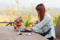 Muchacha que trabaja en su ordenador portátil afuera Imagen de archivo