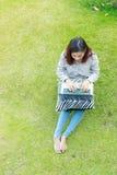 Muchacha que trabaja en su ordenador portátil afuera en césped verde Imágenes de archivo libres de regalías
