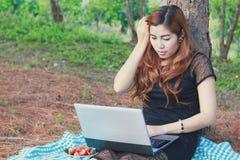 Muchacha que trabaja en su ordenador portátil afuera en el parque Fotografía de archivo libre de regalías