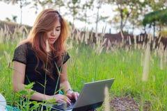Muchacha que trabaja en su ordenador portátil afuera en hierba de prado Fotografía de archivo libre de regalías
