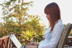 Muchacha que trabaja en su ordenador portátil afuera en la terraza Imagenes de archivo