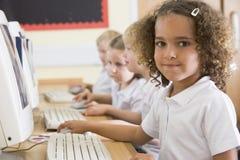 Muchacha que trabaja en un ordenador en la escuela primaria Imágenes de archivo libres de regalías