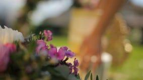 Muchacha que trae en una actual decoración lujosa del regalo para una composición floral del verano al aire libre para la decorac almacen de video