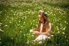 Muchacha que trenza una guirnalda de manzanillas en un campo de la manzanilla Imágenes de archivo libres de regalías
