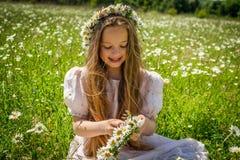 Muchacha que trenza una guirnalda de manzanillas en un campo de la manzanilla Imagenes de archivo