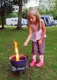 Muchacha que tuesta las melcochas en el fuego del campo imagenes de archivo