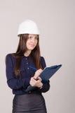 Muchacha que un casco escribe en carpeta del lápiz Fotografía de archivo libre de regalías