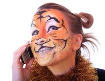 Muchacha que un tigre habla en un teléfono móvil. Foto de archivo libre de regalías
