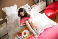 Muchacha que usa el móvil mientras que desayuno en cama Fotos de archivo libres de regalías