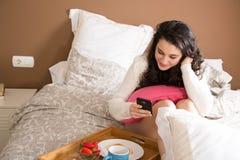 Muchacha que usa el móvil mientras que desayuno en cama Imagenes de archivo
