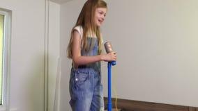 Muchacha que usa el micrófono del juguete metrajes