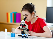 Muchacha que usa el microscopio Imágenes de archivo libres de regalías