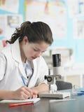 Muchacha que usa el microscopio y tomando notas Fotos de archivo libres de regalías