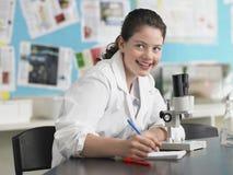 Muchacha que usa el microscopio y tomando notas Foto de archivo