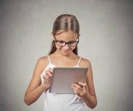 Muchacha que usa el ordenador del cojín que juega al juego Foto de archivo libre de regalías