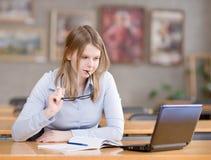 Muchacha que usa el ordenador en una biblioteca Foto de archivo libre de regalías