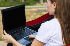 Muchacha que usa el ordenador portátil al aire libre, concepto de tecnología moderna imagenes de archivo