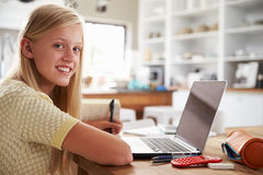 Muchacha que usa el ordenador portátil en casa Fotografía de archivo libre de regalías