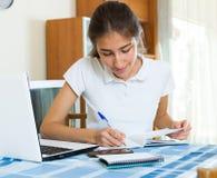 Muchacha que usa el ordenador portátil en casa Foto de archivo