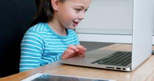 Muchacha que usa el ordenador portátil en casa 4k almacen de metraje de vídeo
