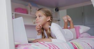 Muchacha que usa el ordenador portátil en dormitorio en el hogar cómodo 4k metrajes
