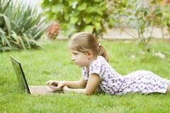 Muchacha que usa el ordenador portátil en el prado Imagen de archivo libre de regalías