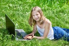 Muchacha que usa el ordenador portátil en hierba Fotografía de archivo libre de regalías