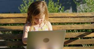 Muchacha que usa el ordenador portátil en el jardín 4k almacen de metraje de vídeo