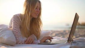 Muchacha que usa el ordenador portátil en la playa 4k almacen de video