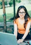 Muchacha que usa el ordenador portátil en el parque Fotografía de archivo libre de regalías