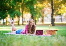 Muchacha que usa el ordenador portátil en un parque Imagen de archivo