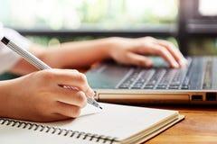 Muchacha que usa el ordenador portátil y la nota Fotografía de archivo libre de regalías