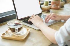 Muchacha que usa el ordenador portátil y mostrando una pantalla en blanco que se sienta en un sofá Foto de archivo