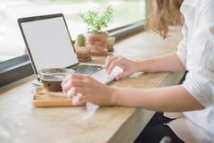 Muchacha que usa el ordenador portátil y mostrando una pantalla en blanco que se sienta en un sofá Fotos de archivo libres de regalías