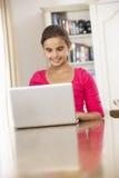 Muchacha que usa el ordenador portátil en casa Foto de archivo libre de regalías