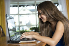 Muchacha que usa el ordenador portátil en casa Imágenes de archivo libres de regalías