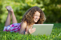 Muchacha que usa el ordenador portátil mientras que miente en hierba Imagen de archivo libre de regalías