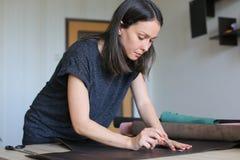 Muchacha que usa el permiso por maternidad para hacer los accesorios de cuero Imagenes de archivo