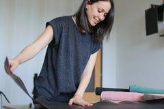 Muchacha que usa el permiso por maternidad para hacer los accesorios de cuero Foto de archivo libre de regalías