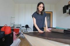 Muchacha que usa el permiso por maternidad para hacer los accesorios de cuero Imágenes de archivo libres de regalías