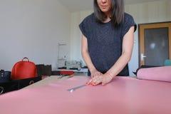 Muchacha que usa el permiso por maternidad para hacer los accesorios de cuero Fotos de archivo