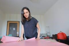 Muchacha que usa el permiso por maternidad para hacer los accesorios de cuero Imagen de archivo
