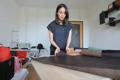 Muchacha que usa el permiso por maternidad para hacer los accesorios de cuero Fotografía de archivo